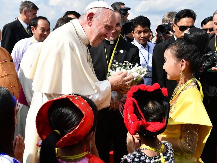 Pope Francis is greeted by children upon his arrival at Yangon International Airport