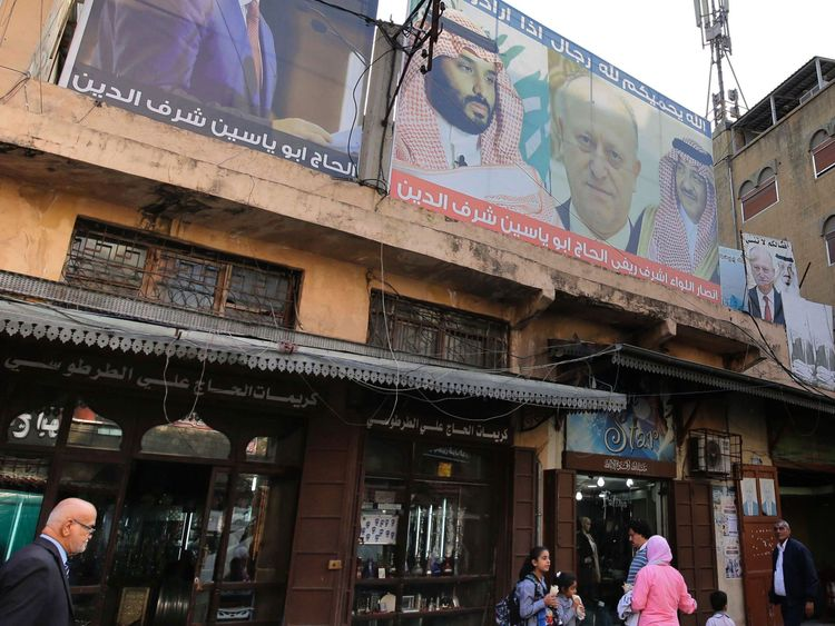 Lebanese pedestrians walk past shops decorated with posters bearing pictures of Saudi Arabia's Crown Prince Mohammed bin Salman (L), his predecessor, ousted crown prince Mohammed bin Nayef (3rd R), and King Salman bin Abdul Aziz (R), in a show of support to the Saudi leadership in the bazaar of the northern Lebanese port city of Tripoli on November 8, 2017. Lebanon's former prime minister Saad Hariri announced his resignation last weekend from the Saudi capital Riyadh in a televised speech which