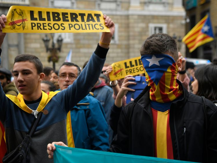 A man wears a Catalan flag as a mask
