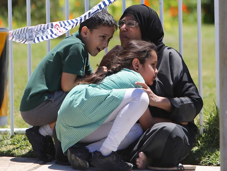 A woman hugs her children near the school