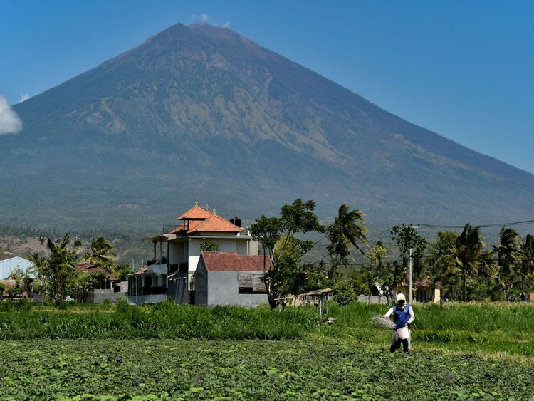 A farmer fertilizers his field at the base of Mount Agung volcano, in Karangasem Regency on the Indonesian resort island of Bali on September 27, 2017. Indonesian authorities are ready to divert flights to and from the holiday island of Bali as increasingly frequent tremors from a rumbling volcano stoke fears an eruption could be imminent. / AFP PHOTO / BAY ISMOYO (Photo credit should read BAY ISMOYO/AFP/Getty Images)