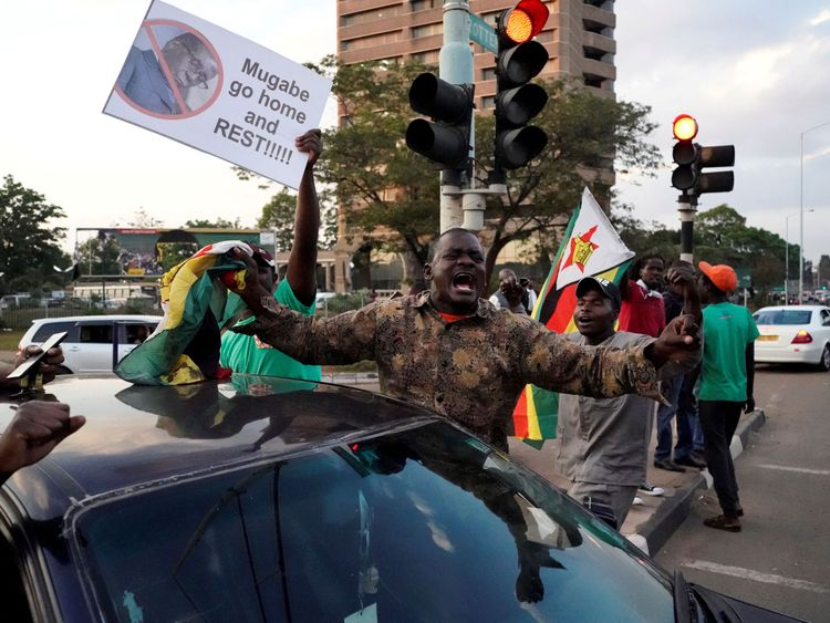 People celebrate in the streets after the resignation of Zimbabwe's president Robert Mugabe