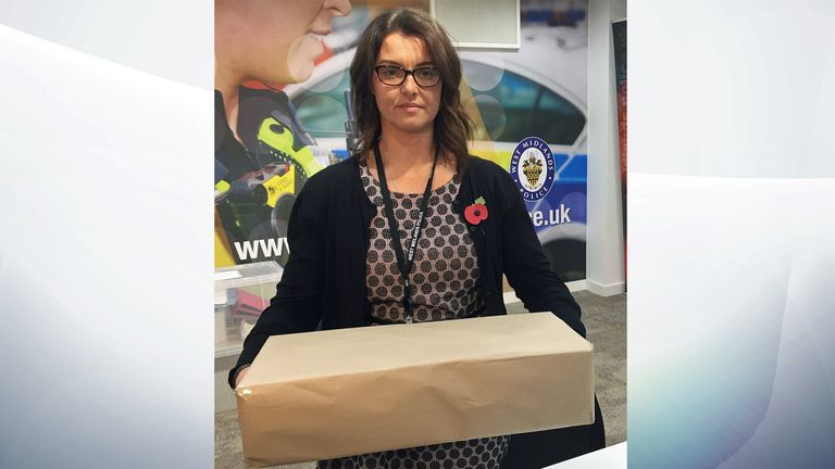 DCI Sarah Burton of West Midlands Police holding a box the size of a multi-shot firework used in the arson attack
