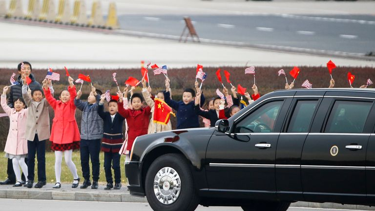 Chinese children wave to Mr Trump after he arrives in Beijing