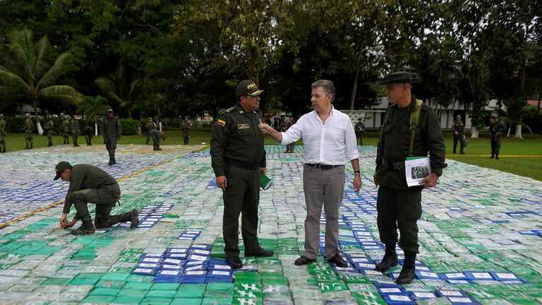 Colombia's president Juan Manuel Santos stands on the huge haul of cocaine - laid out like a carpet in Apartado