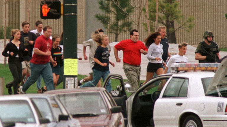 People flee from Columbine High School during the mass shooting