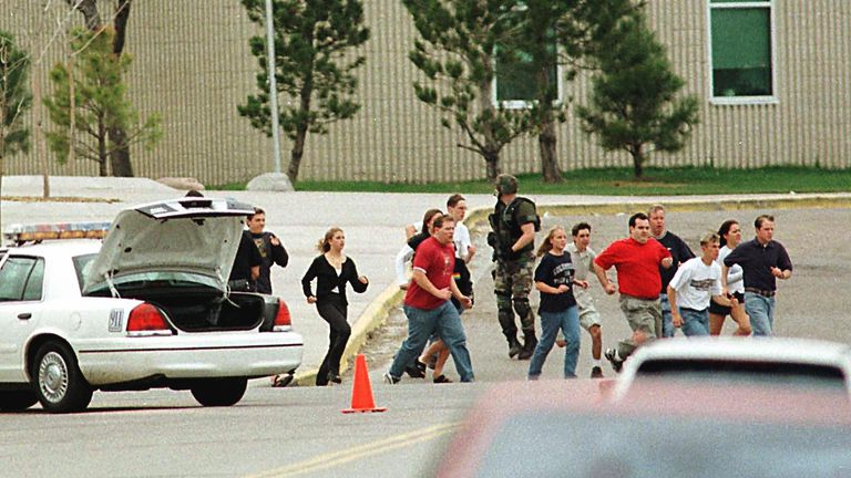 Students run from Columbine High School run under cover from police on 20 April 1999