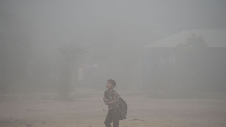 An Indian schoolboy walks along a road amid heavy smog in the old quarters of Delhi