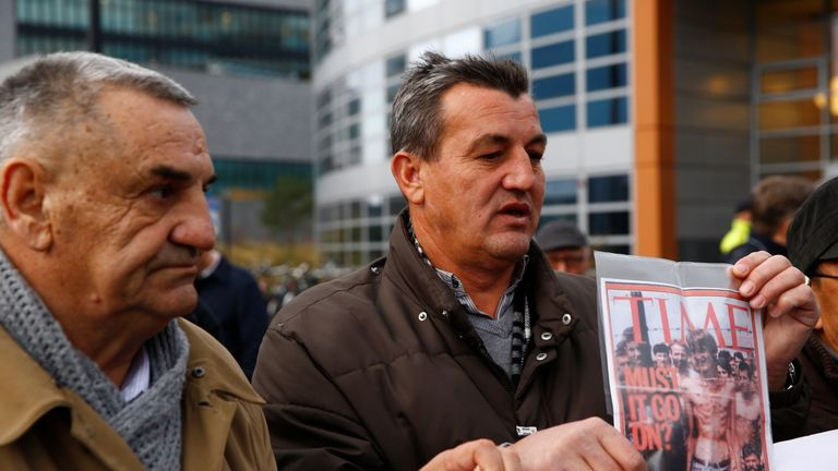 Fikret Alic, one of the survivors of concentration camps shows his photo on the cover of Time