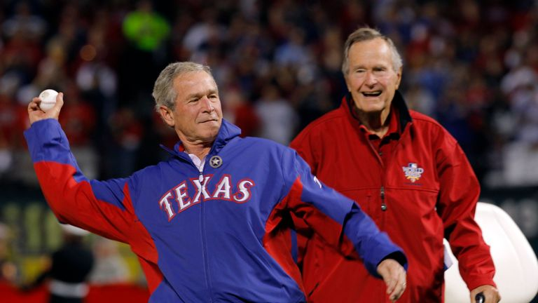 Former U.S. President George H.W. Bush (R) watches as his son, former President George W. Bush, throws a ceremonial first pitch prior to the start of a match between the San Francisco Giants and the Texas Rangers, in Arlington, Texas, October 31, 2010