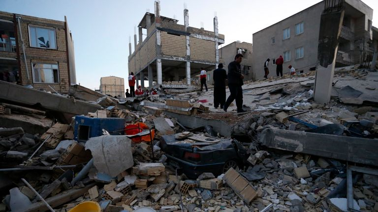 People including rescue personnel conduct search and rescue work following a 7.3-magnitude earthquake at Sarpol-e Zahab in Iran's Kermanshah province on November 13, 2017. At least 164 people were killed and 1,600 more injured when a 7.3-magnitude earthquake shook the mountainous Iran-Iraq border triggering landslides that were hindering rescue efforts, officials said