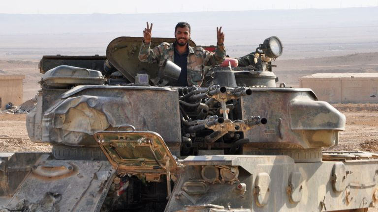 A soldier from the Syrian government forces flashes the 'V' for victory sign
