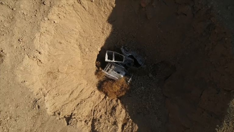 Cars can be seen at the base of the sinkhole