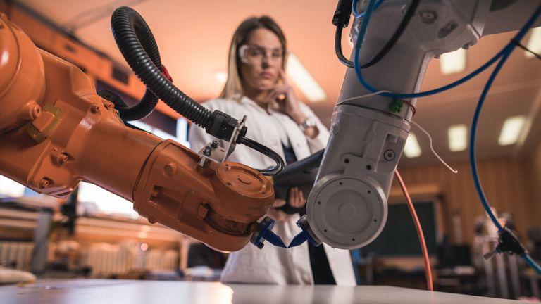 Two robotic arms manufacturing something in laboratory while female engineer is in the background.