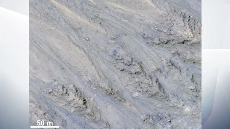 This HiRISE image cutout shows Recurring Slope Lineae on Mars in enhanced color. The narrow, dark flows descend downhill (towards the upper left). Analysis shows that the flows all end at approximately the same slope, which is similar to the angle of repose for sand.​​​​​​​ Credit: NASA/JPL/University of Arizona/USGS. Public domain.​​​​​