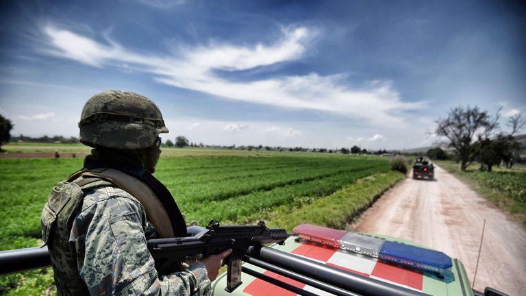 A Mexican army soldier patrols a clandestine fuel siphoning area in Tepeaca, Puebla