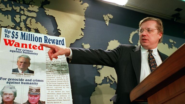 David Scheffer, US Ambassador at large for war crimes, points to a poster showing Slobodan Milosevic, Radovan Karadzic and Ratko Mladic