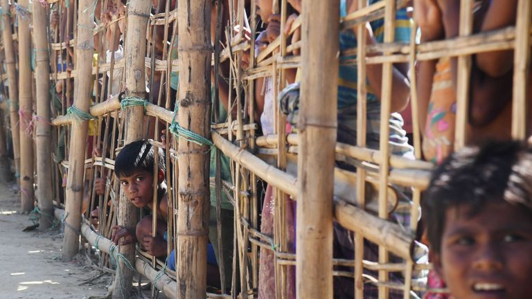 A young boy peeps through a bamboo barricade at the Thankhali refugee camp, Bangladesh