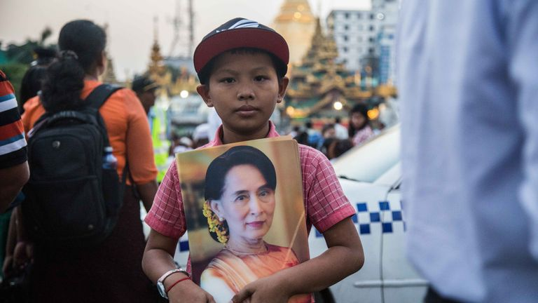 A young Myanmar boy holds a poster of Aung San Suu Kyi during an interfaith prayer ceremony organized by the National League for Democracy in front of City Hall on October 31, 2017 in Yangon