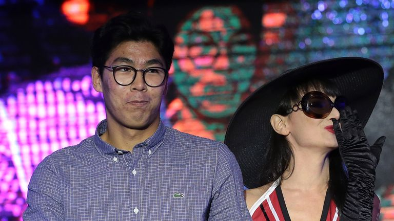 Hyeon Chung walks the runway with a model during the draw
