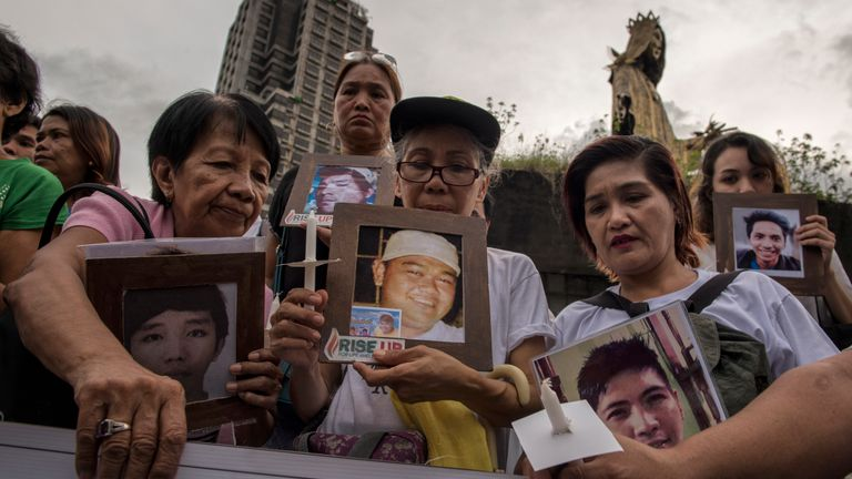 Demonstrators hold pictures of family members killed in the war on drugs