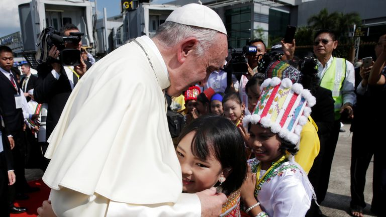 A girl embraces Pope Francis as he arrives at Yangon International Airport, Myanmar