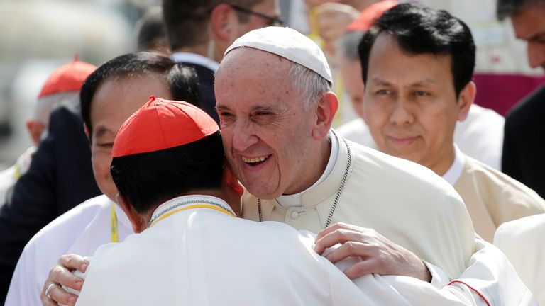 Pope Francis is embraced as he arrives at Yangon International Airport