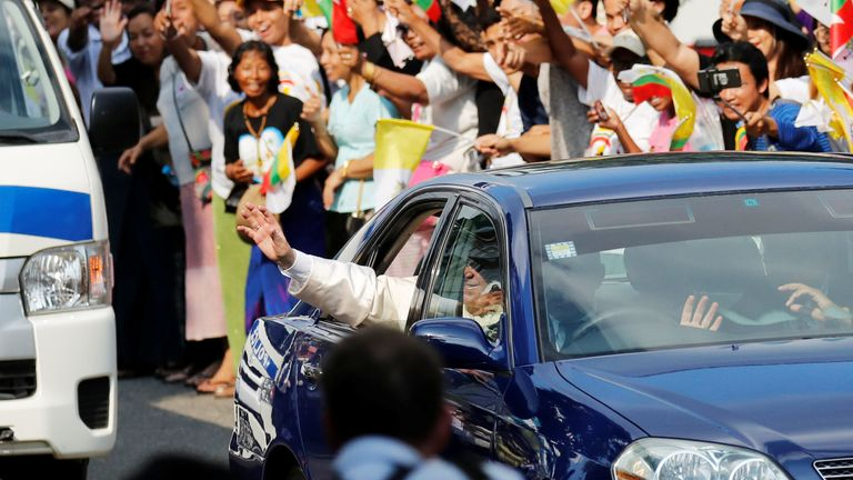 Pope Francis waves as his car travels past well-wishers in Yangon