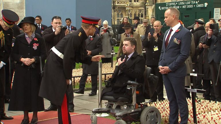 Prince Harry talks with veterans outside Westminster Abbey