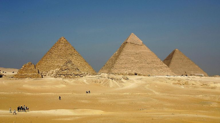 GIZA, EGYPT - NOVEMBER 13: The three large pyramids of Menkaure (L), Khafre (C) and Khufu loom over the horizon November 13, 2004 at Giza, just outside Cairo, Egypt. The three large pyramids at Giza, built by King Khufu over a 30 year period around 2,550 B.C., are among Egypt's biggest tourist attractions.  (Photo by Sean Gallup/Getty Images)....