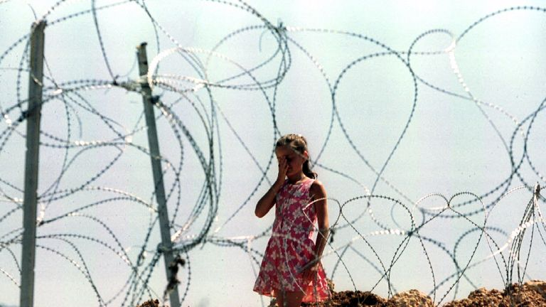 A young girl cries in the cemetery in Sarajevo, August 1994.
