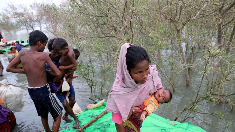 Rohingya refugees walk after crossing the Naf River with an improvised raft to reach Bangladesh