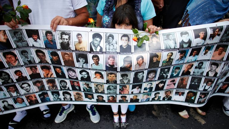 A child holds a poster with portraits of people killed at Srebrenica