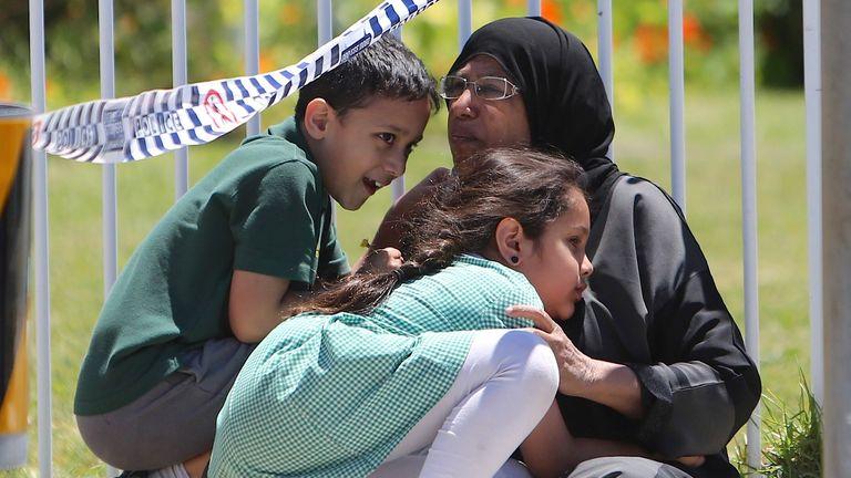 A woman hugs her children near the school