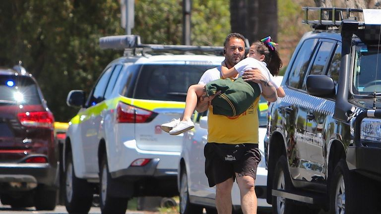 A man carries a young girl away from the scene of the horrific crash