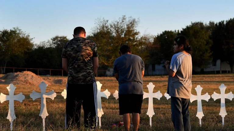 People pray at a row of crosses for each victim, after a mass shooting that killed 26 people in Sutherland Springs, Texas on November 6, 2017