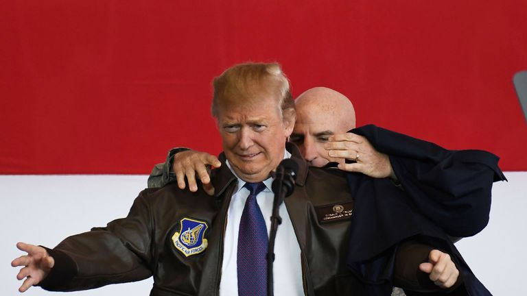 US President Donald Trump (L) receives a bomber jacket from the US Pacific Air Forces