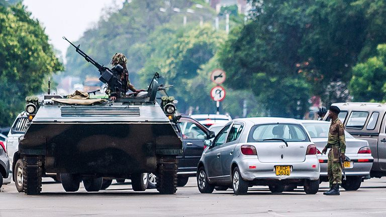 An armoured personnel carrier stations by an intersection as Zimbabwean soldiers regulate traffic in Harare