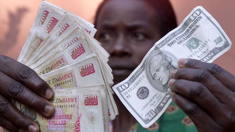 A Zimbabwean holds a ten U.S. dollar bill and the black market