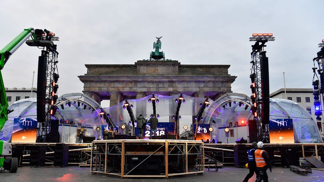 People prepare the stage for New Year's Eve festivities in front of Berlin's landmark Brandenburg Gate on December 30, 2017. / AFP PHOTO / John MACDOUGALL (Photo credit should read JOHN MACDOUGALL/AFP/Getty Images)