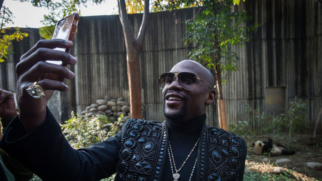 Floyd Mayweather Jr taking a photo with his own giant panda