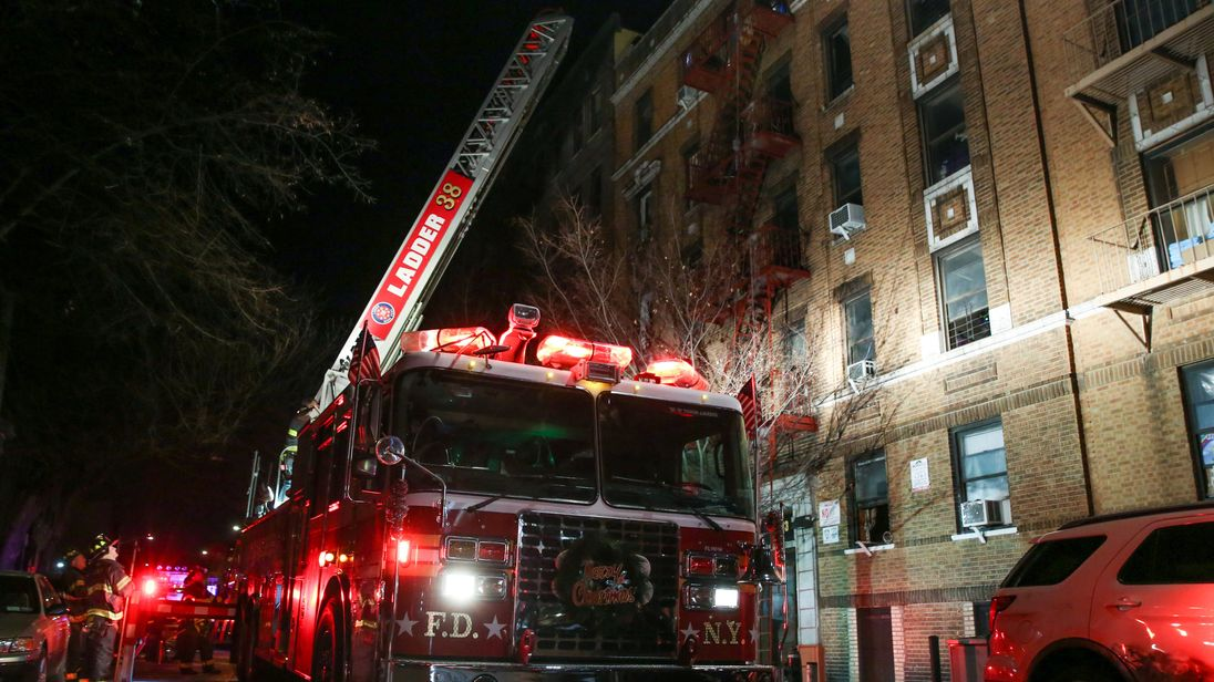 Fire Department of New York (FDNY) personnel work on the scene of an apartment fire in Bronx, New York