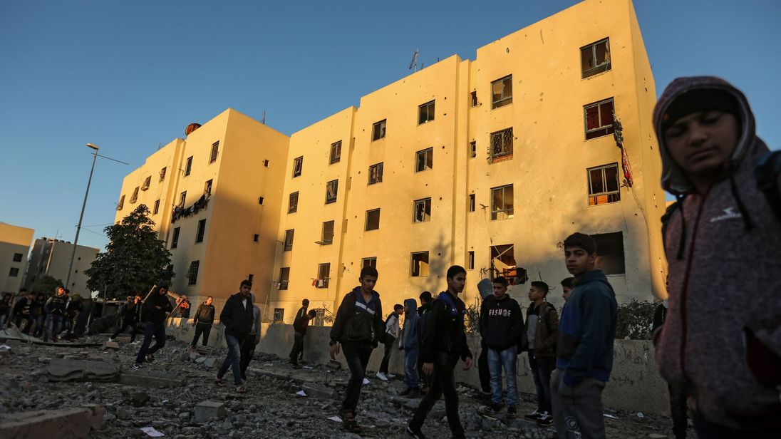 Palestinians look at the damage in the aftermath of an Israeli air strike in Beit Lahia