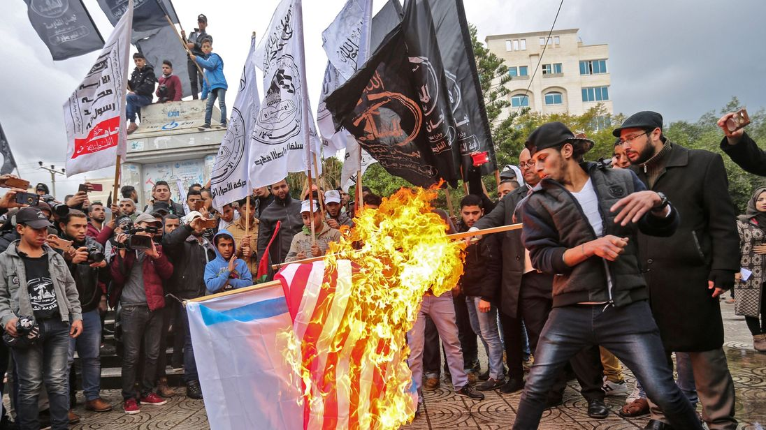 Palestinian protesters burn the US and Israeli flags in Gaza City
