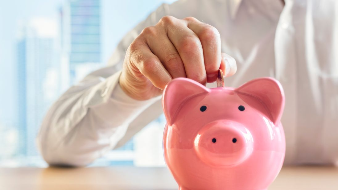 Man putting a coin into a pink piggy bank concept for savings and finance