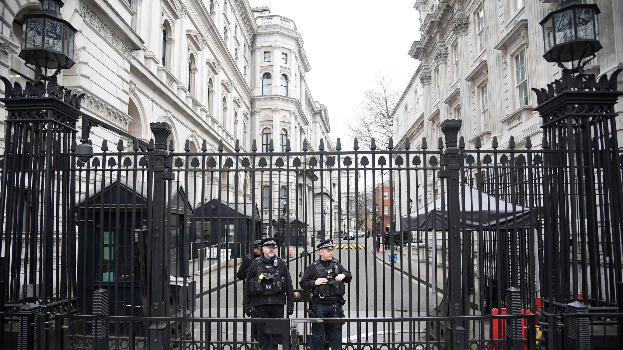 Armed police officers stand guard at the gates of Downing Street