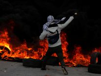 A Palestinian protester hurls stones towards Israeli troops during clashes in Ramallah