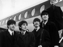 1964:  British pop phenomenon The Beatles standing on the steps of an aeroplane at London Airport