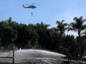 An US military helicopter from Camp Pendleton makes a water drop