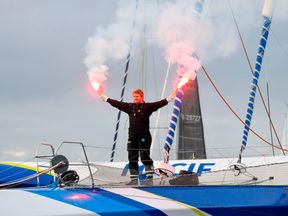 Francois Gabart celebrates aboard his trimaran, Macif, at the end of his epic journey